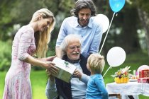 Grandfather receiving gift on birthday party in garden — Stock Photo