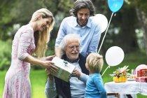 Nonno che riceve il regalo sulla festa di compleanno in giardino — Foto stock