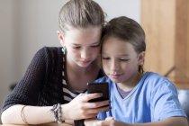 Портрет брата и сестры, смотрящих на смартфон дома — стоковое фото