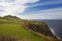 Portugal, Azores, Sao Miguel, Lighthouse Farol da Ponta da Ferraria against water on cliff — Stock Photo