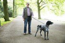 Senior homme marchant avec chien dans le parc — Photo de stock