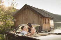 Couple sitting in vintage car convertible in front of wooden hut at Schliersee — Stock Photo