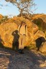 Montañas de África, Namibia, Erongo, caminante de pie delante de la roca al atardecer - foto de stock