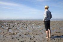 Alemania, Baja Sajonia, Nessmersiel, mujer mirando al mar de wadden - foto de stock