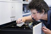 Женщина-техник в мастерской по электронике — стоковое фото