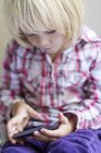 Little girl playing with smartphone — Stock Photo