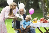 Grandfather receiving gifts on birthday party in garden — Stock Photo