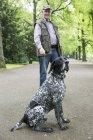 Старший людина з собакою в міському парку — стокове фото