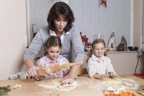 Mutter backt mit ihren beiden Töchtern Weihnachtsplätzchen — Stockfoto