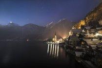 Ночной вид на Халл и озеро с горами Фаштайн в австрийском городе Мергут — стоковое фото
