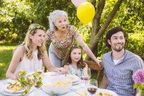 Happy family of three generations on a garden party — Stock Photo