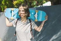 Mujer skate boarder holding skateboard - foto de stock