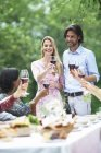 Couple holding glasses of red wine on a garden party — Stock Photo
