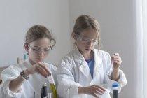Due pupille facendo esperimento chimico — Foto stock