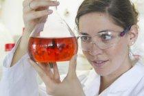 Женщина-химик держит фляжку Эрленмейера — стоковое фото