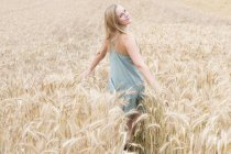 Portrait of smiling young woman with outstretched arms standing in a rye field — Stock Photo