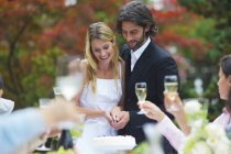 Bride and groom cutting wedding cake on a garden party — Stock Photo