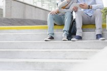 Two young men sitting on stairs using digital tablet — Stock Photo