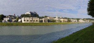 Австрія, Зальцбург, вид з річку Зальцах на замок Хоензальцбург над водою — стокове фото