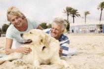 Smiling couple de personnes âgées avec chien sur la plage de sable fin — Photo de stock