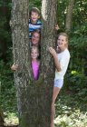 Portrait of friends standing behind tree trunk, smiling — Stock Photo