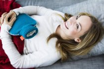 Portrait of young woman lying on couch with hot water bottle, smiling — Stock Photo