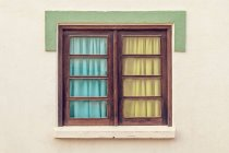 Closed window with colored curtains in Portugal — Stock Photo