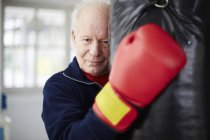 Senior man with boxing glove embracing punch bag — Stock Photo