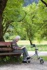 Старший жінка, сидячи на лавці і читання книги — стокове фото