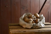 Organic brown mushrooms in paper on wooden crate — Stock Photo