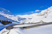 Cars on the road in snowy winter mountains, alpine, mountain pass, Julier Pass, Grisons, Switzerland — Stock Photo