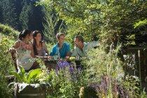 Family chatting with drinks in alpine garden, Salzburg, Austria — Stock Photo