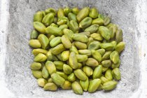 Close-up of raw pistachio kernels in dish — Stock Photo