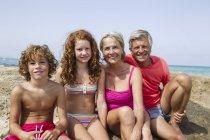 Дідусі та бабусі з онуками, сидячи на пляжі — стокове фото