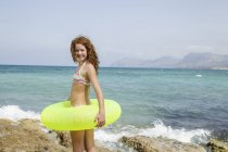 Girl with swim ring standing on rock — Stock Photo