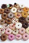 Muchos dulces donas coloridas sobre fondo blanco - foto de stock