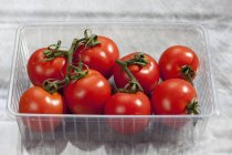 Vine tomatoes in plastic box — Stock Photo