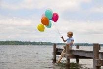 Germania, Baviera, Ragazzo seduto sul molo e con palloncini colorati al lago Starnberg — Foto stock