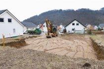 Uomo che prepara il terreno per fondamenta di una casa con veicolo di scavo — Foto stock