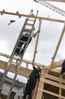 Men working on roof of house building — Stock Photo