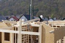 Men assembling roof ridge of prefabricated house — Stock Photo