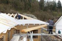 Trabajadores del material para techos de casa en obra - foto de stock