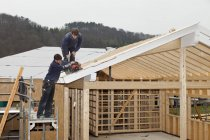 Manual workers roofing on wooden house — Stock Photo