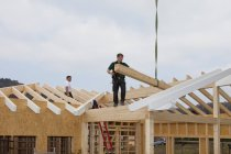 Men working on roof of building shell — Stock Photo