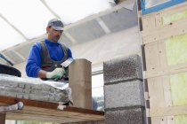 Чоловічий працівник встановлення теплових ізоляційних на будмайданчик — стокове фото