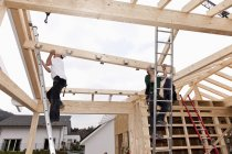 Men working on roof of house on construction site — Stock Photo