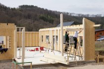 Men installing and fixing wooden walls of prefabricated house — Stock Photo