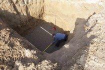 Homme d'âge mûr mesurant la fosse pour l'installation de citerne d'eau de pluie — Photo de stock