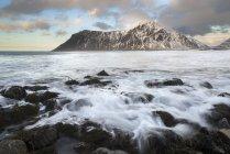 Norwegen, Lofoten, Flakstad felsigen Strand bei Sonnenuntergang mit Berg im Hintergrund — Stockfoto