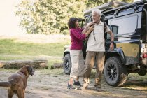 Senior couple standing next to cross country vehicle and preparing for a hiking — Stock Photo